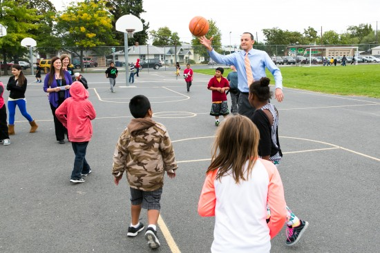 Rep. Riccelli on playground at Stevens Elementary playing basketball with children