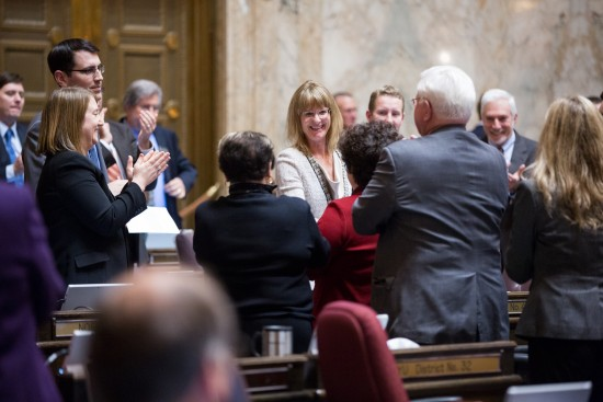 Rep. Patty Kuderer (D-Clyde Hill) is congratulated by her colleagues after the passage of her first bill on the House floor.
