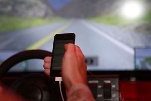 Photo of hand holding cell phone while driving