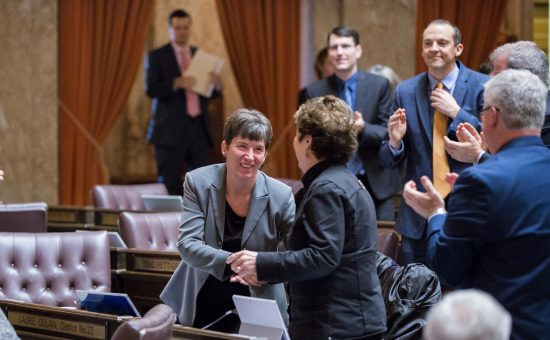 Rep. Laurie Dolan (D-Olympia) is congratulated by her colleagues after her first bill wins approval by the House of Representatives.