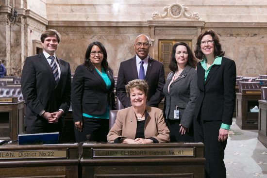 Rep. John Lovick (D-Mill Creek, center) on the floor of the House of Representatives with Rep. Mike Pellicciotti, Rep. Krstine Reeves, Transportation Chair Rep. Judy Clibborn (seated), Rep. Shelley Kloba and Rep. Christine Kilduff.