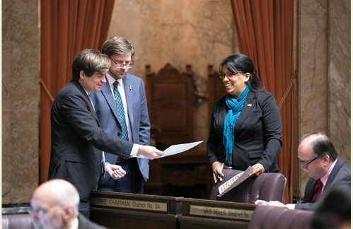 Rep. Mike Chapman (D-Port Angeles) working on the floor of the House of Representatives with Rep. Mike Pellicciotti, left, and Rep. Kristine Reeves, right.