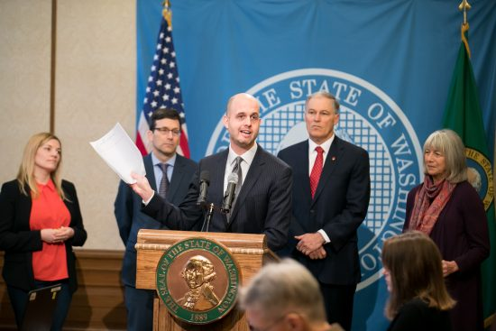 Rep. Drew Hansen holds a copy of his net neutrality bill, HB 2282, during a press conference in the Governor's Office