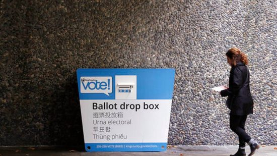 Woman takes ballot to drop box