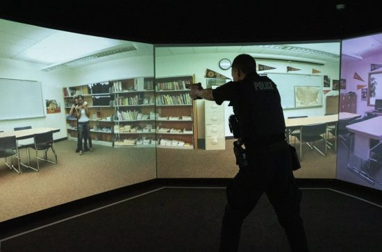 In a simulated hostage situation, Camas police Officer Kevin Hermann points his gun in a training apparatus at the Criminal Justice Training Center in Burien.