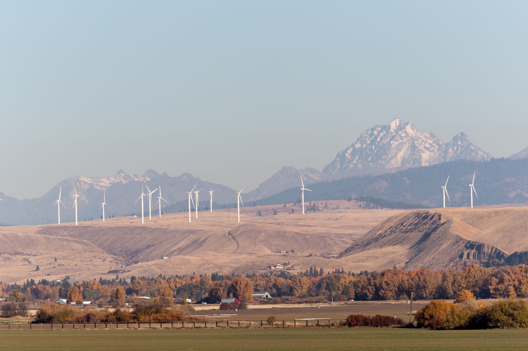 View of Mt. Stuart from Ellensburg, in the foreground are farms and windmills