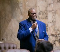 Rep Pettigrew speaking on the House floor in a blue suit