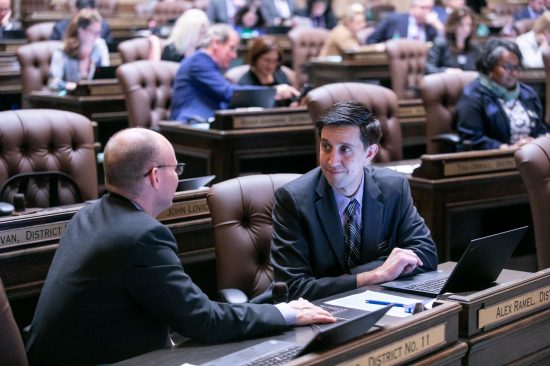 Rep. ALex Ramel at his desk on the floor