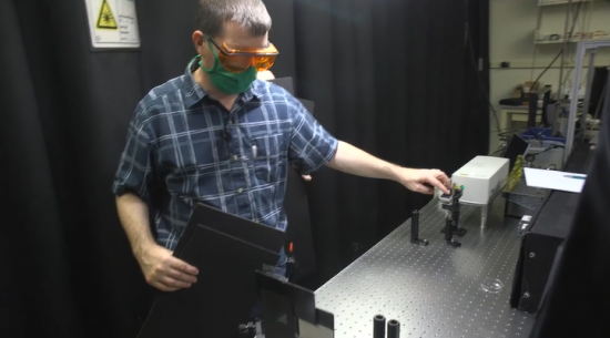 A man in a blue plaid shirt, green mask, and orange safety goggles holds a device over a metal table.