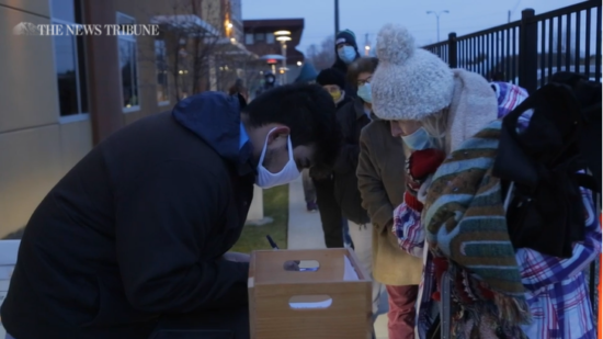 A video screenshot shows a line of masked people standing outside. They are approaching a masked person who is writing something on a table near a box of papers.
