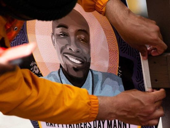 A pair of hands tapes down an illustrated poster depicting Manny Ellis smiling in a blue shirt.