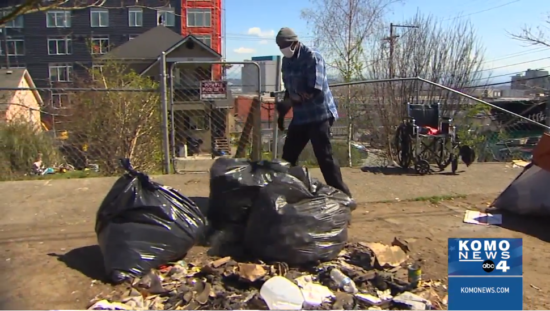 On a sunny day, black trash bags sit in a pile on the ground as a masked man stands nearby. A metal fence and a building are in the background.