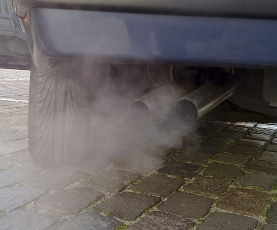 On dark gray cobblestones, the back corner of a car's bumper and back tire are shown, with its tailpipes blowing out exhaust.