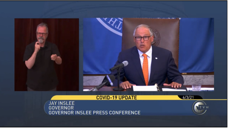 A video shot at a press conference of an ASL interpreter on the left and Gov. Inslee on the right announcing Washington state's vaccine lottery incentive.