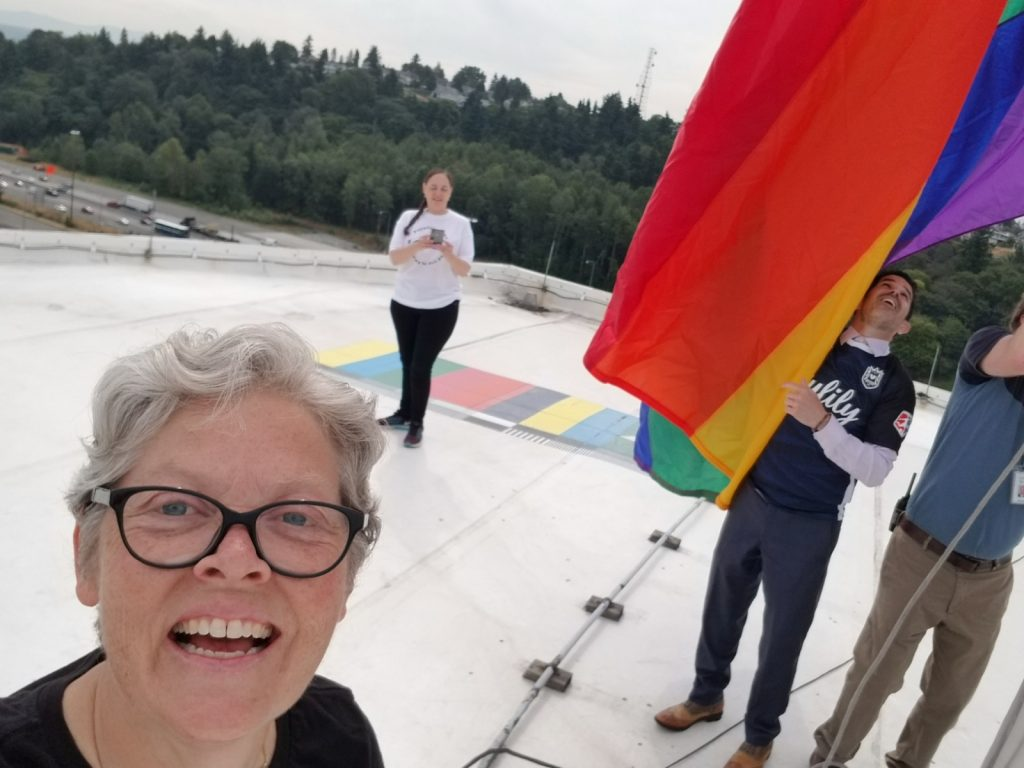 Rep. Jinkins selfie on top of Tacoma Dome with Pride flag