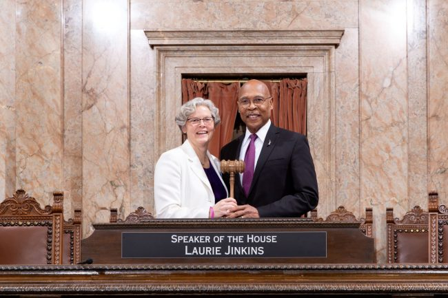 Speaker Laurie Jinkins (D-Tacoma) Deputy Speaker Pro Tempore John Lovick (D-Mill Creek) at the House rostrum jointly holding gavel.