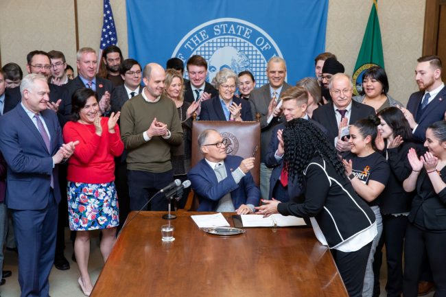 Bill signing in the governor's office for SB 6492 - legislators and advocates surround governor and applaud