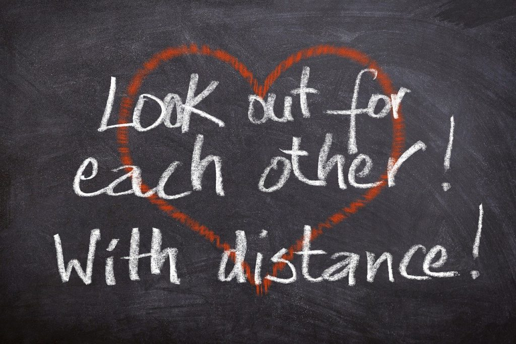 "Red heart on chalkboard with ""Look out for each other! With distance!"" written over it"