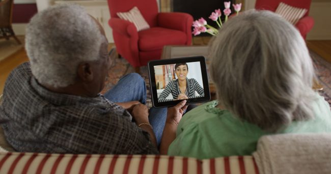 African American elderly couple on couch video chatting with granddaughter.