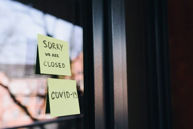 "Two yellow post it notes on glass door that say Sorry We are closed and ""Covid 19"""