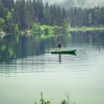 man standing up in small boat in middle of lake fishing; lake surrounded by evergreens