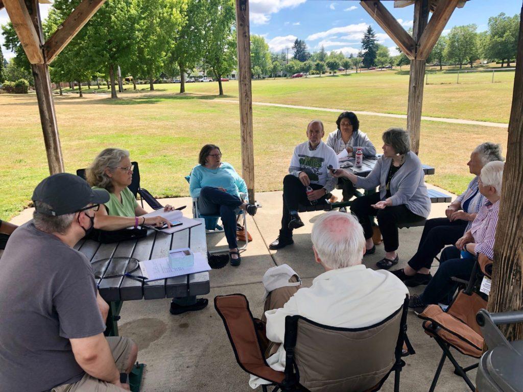 Legislators under picnic shelter chatting with constituents