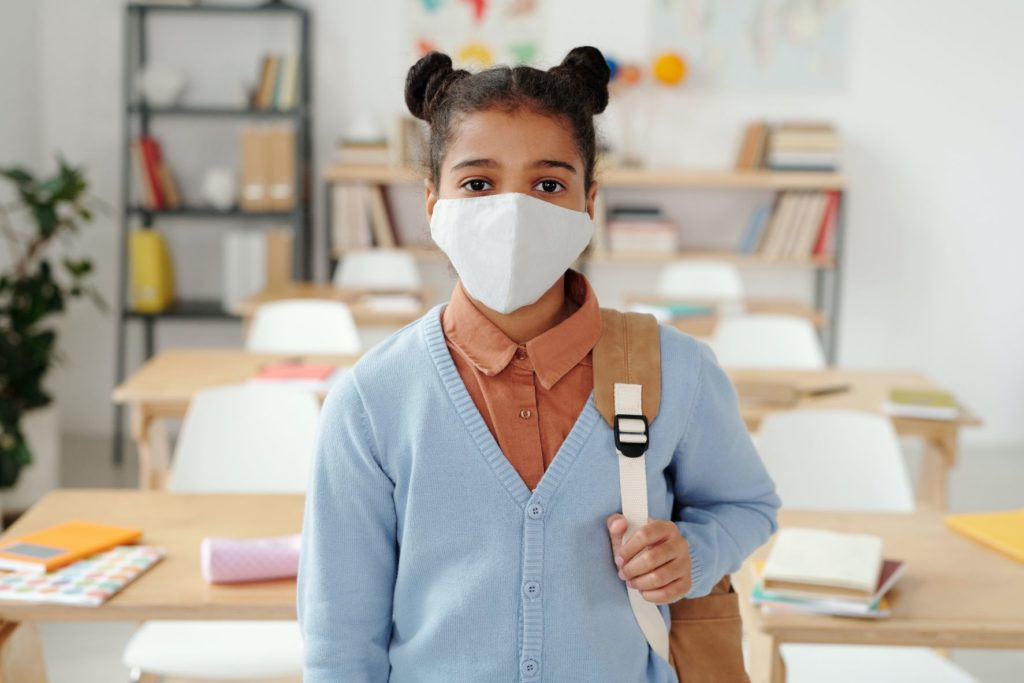 Student with mask and backpack in classroom