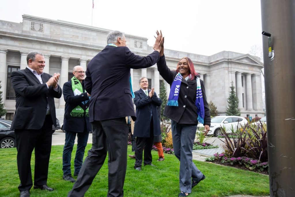 Rep. Morgan and Governor Inslee high five in the flag circle